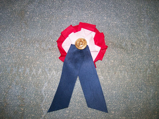 Reproduction 1861 union cockade: red, white, and blue silk ribbon with uniform button.