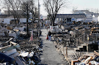 Louise McCarthy carts her belongings through the fire-charred ruins of the Breezy Point section of Queens after Superstorm Sandy brought floods, fires and blackouts to New York City. New studies show future risks of such storms will be worse. (Credit: Photo by Mark Lennihan / AP Images.) Click to Enlarge.