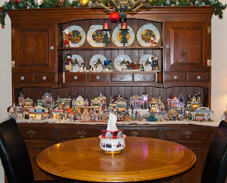 Part of a Christmas village on display in a wooden cabinet.