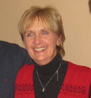 Smiling blond woman wearing a black turtleneck and red sweater stands in front of a tan wall