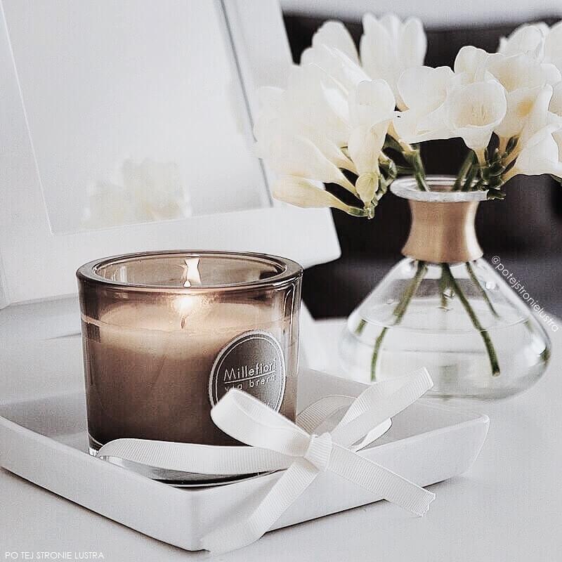 świeca millefiori earl grey i bukiet białych frezji na komodzie