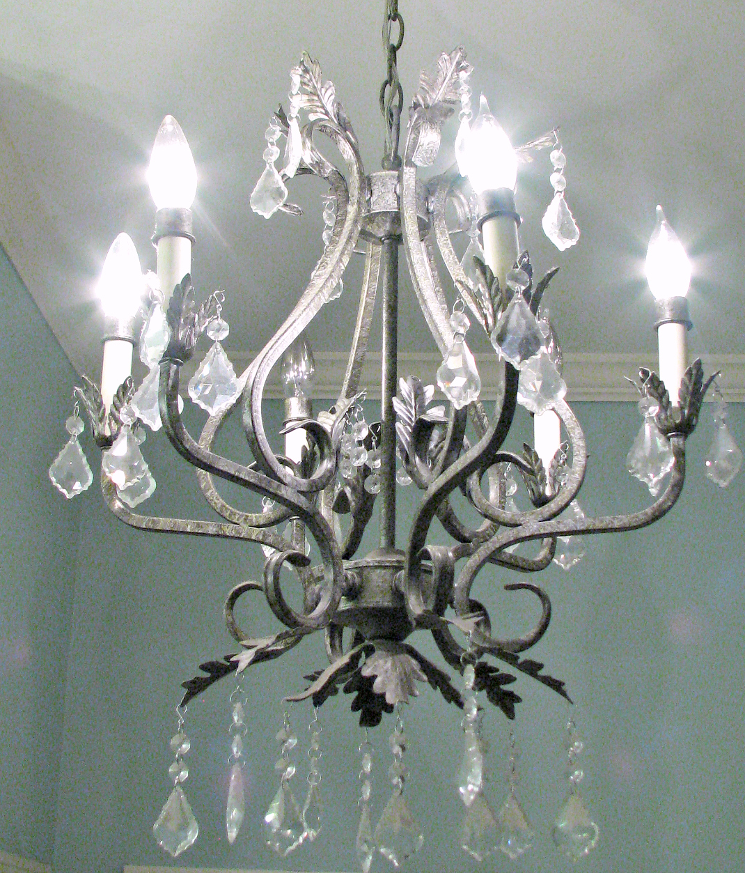 small wrought iron chandelier in bathroom with crystals