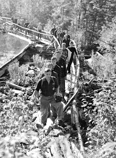 A line of men walking along a bridge.