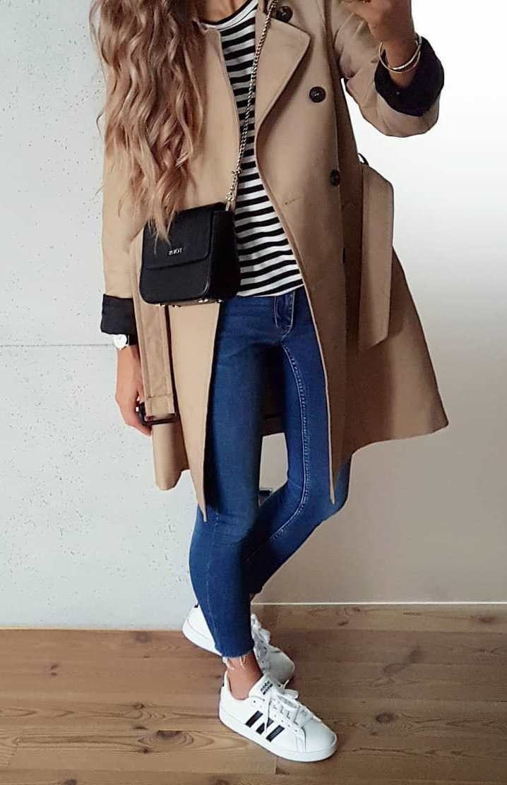 trendy fall outfit idea for this season / striped top + black bag + nude coat + skinny jeans + sneakers