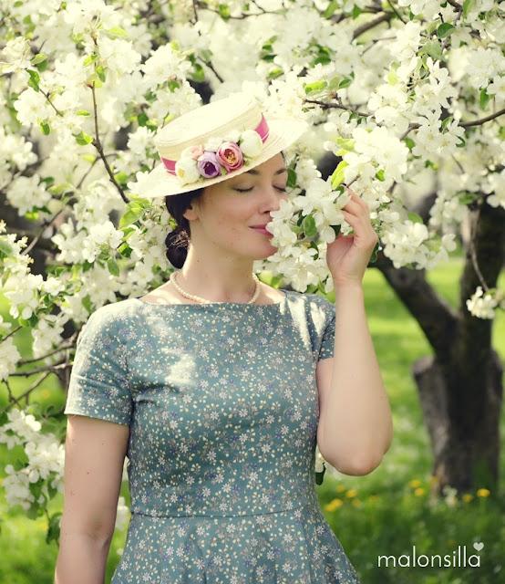 Chica de piel clara y ojos azules con sombrero de flores y almendros en flor en Moscú