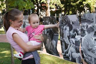 Unul din micile modele care are fotografie expusă la Hrană pentru suflet își privește portretul