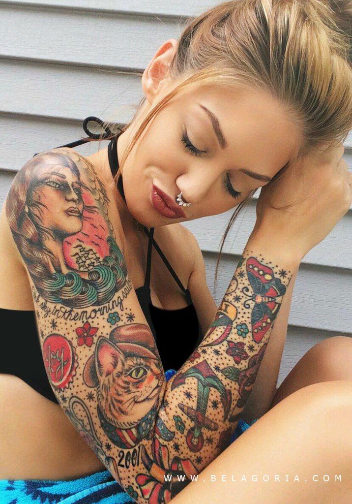 Chica rubia sonriendo sentada, lleva tatuajes en el brazo de estilo old school en vivos colores