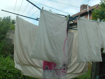 Photo of sheets and pillowcases on a laundry line in a garden