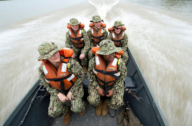 Five people in military fatigues sit in a boat speeding down a river. A team of five U.S. Navy doctors travel to a remote village along the Amazon River in Brazil; (clockwise from left) Lt. Cmdr. Patricia Hogan, internal medicine specialist; Lt. Cmdr. Robert P. Lennon, specialist in general medicine; Lt. Cmdr. Thomas K. Barlow, specialist in dermatology; Lt. Gregory J. Condos, internal medicine specialist; and Lt. Cmdr. Nehkonti Adams, infectious diseases specialist. The team worked with the Brazilian Navy to deliver healthcare to some of the most isolated people in the world. (Image credit: U.S. Navy photo by Mass Communication Specialist 2nd Class Andrew Brame)