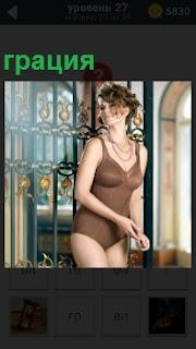 Девушка около окна грация в изящном купальнике, привлекая мужские взгляды и радуя глаза