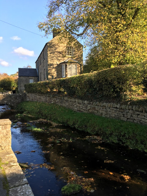stream with stone walls, and a small stone house