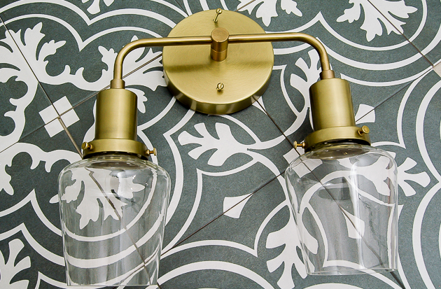 cement inspired tile and brass sconce