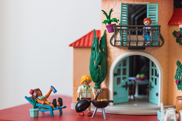 Playmobil summer villa set with the dad barbecuing and the mum on a sun lounger with a bottle of suncream