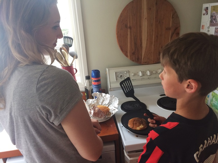 Carina mentoring Scrag on how to make pancakes