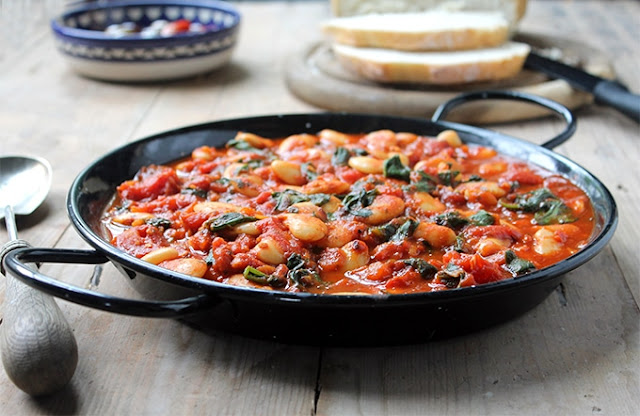 Cooked Spanish Beans with tomatoes in a black skillet