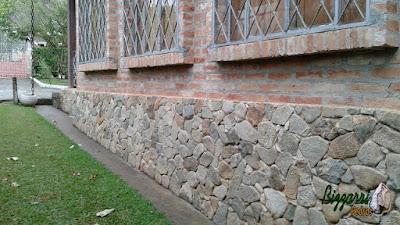 Base da casa com execução do revestimento de pedra com pedra moledo tipo chapas em casa com parede de tijolo a vista em condomínio em Atibaia-SP.
