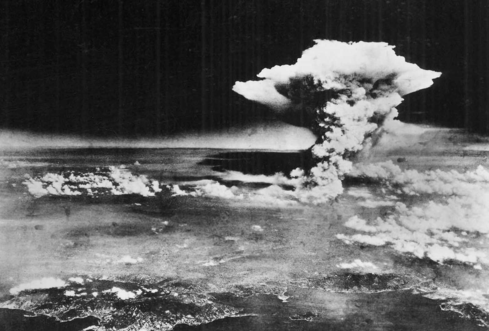 On August 6, 1945, a mushroom cloud billows into the sky about one hour after an atomic bomb was dropped by American B-29 bomber, the Enola Gay, detonating above Hiroshima, Japan. Nearly 80,000 people are believed to have been killed immediately, with possibly another 60,000 survivors dying of injuries and radiation exposure by 1950.