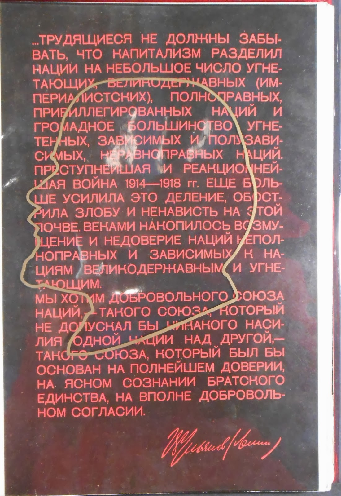 The outline of a profile in front of a block of red Cyrillic text.
