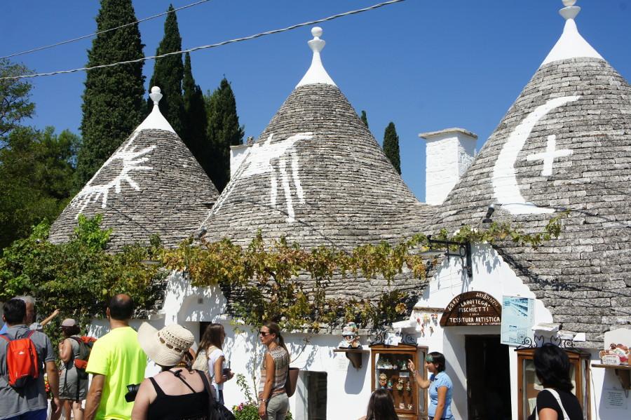 Turisti, negozietti e simboli sui trulli ad Alberobello