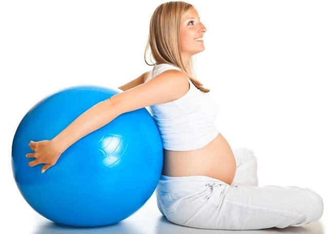 Uma mulher vestida toda de branco segurando uma bola da cor azul e grande, para a pratica de pilates