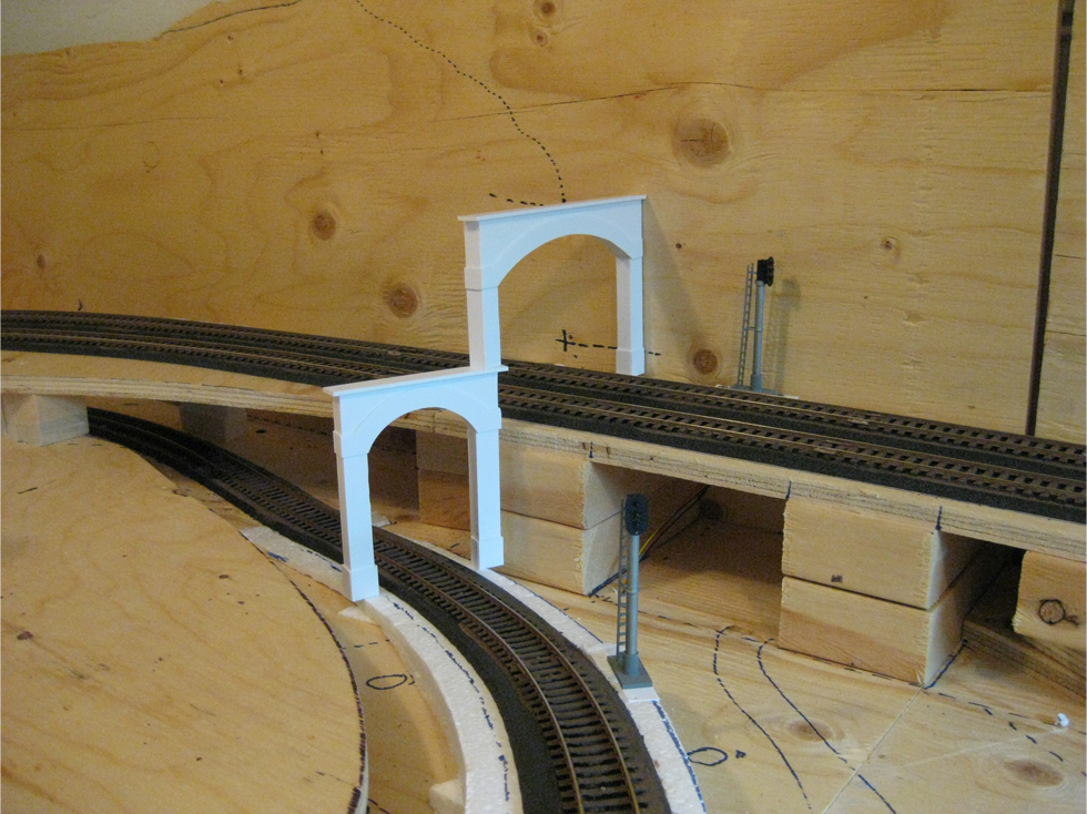 A single and double styrene tunnel portal placed on model railroad track to test fit