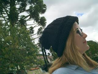 gorro/gola de trico na cor preta na cabeça de uma mulher com óculos