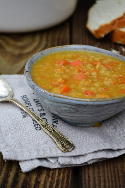 Fridge lentil soup in a ceramic grey bowl on a grey cotton napkin with spoon