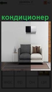 В комнате в черно белых красках находятся диван и на стене висит кондиционер