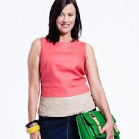 Женщина за 50 в розовом топе с зеленой сумкой
