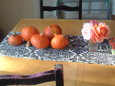 Five small orange squashes on a kitchen table