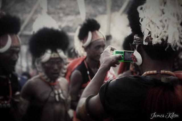A Khiamniungan Naga man takes video of his friends performing folk dance from his mobile