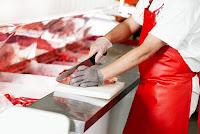 Bıçağıyla tezgahta et doğrayan bir kasap