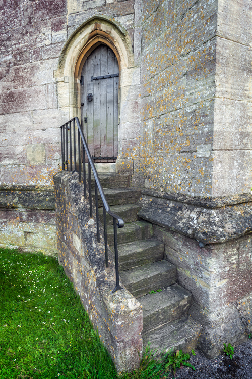 Steps lead to an old wooden door on the side of St. Mary's Church in Painswick