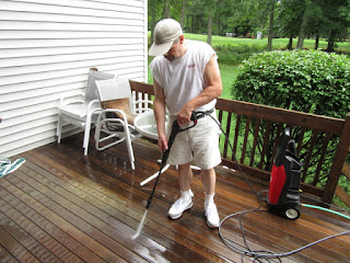 Owner of Jcb Painting power washing deck to clean before painting.