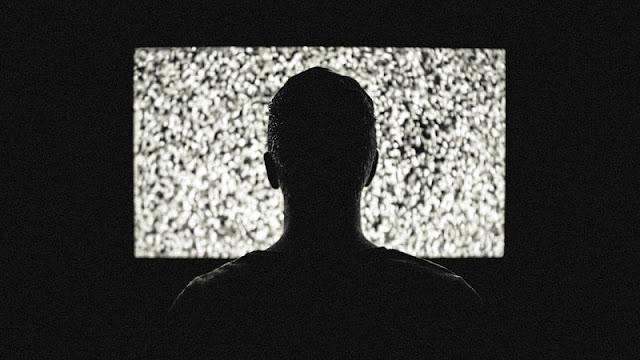 seorang pria sedang menonton televisi dalam kamar yang gelap gulita