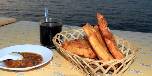 Sajian pisang goreng dan secangkir kopi sambil menikmati suasana sunset di Teluk Manado.(Kompas.com/Ronny Adolof Buol)