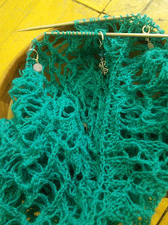 Lace knitting on the needles.  Yarn is a deep turquoise lace-weight yarn, and there are multiple sets of stitch markers clipped into the work.
