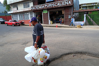 Man carrying empty plastic bottles in Puriscal.