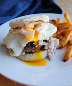Close up of burger on toasted English muffin, topped with creamy bacon gravy and a drippy yolk from a fried egg served with friench fries in the background