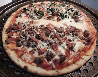 A cooked pizza on the tray, half with beef, spinach and bacon, the other half with beef, bacon and onions.
