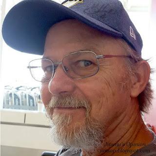 Jimmy looking sideways at camera wearing a denim blue ball cap