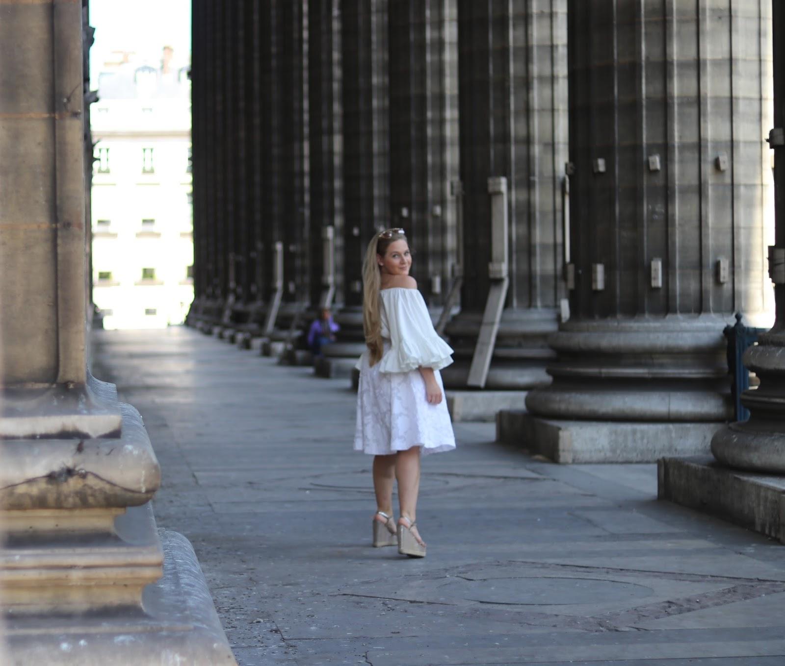 Blonde Girl, Katie Heath wearing all white in front of Pillars, Paris, France
