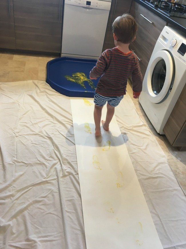 toddler-walking-on-roll-of-paper-towards-tuff-spot-with-paint