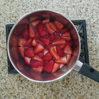 cut up strawberries soaking in simple syrup in a pot