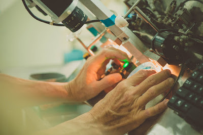 Source: Essilor Singapore. Close-up of hands examining a lens under a microscope.