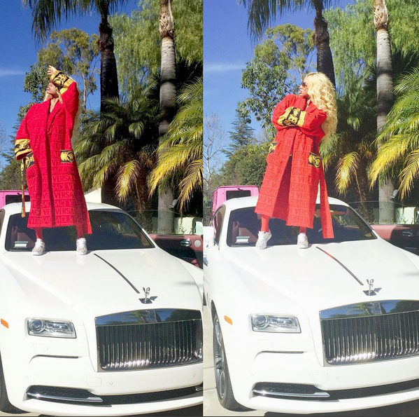 Dencia poses on top of Rolls Royce