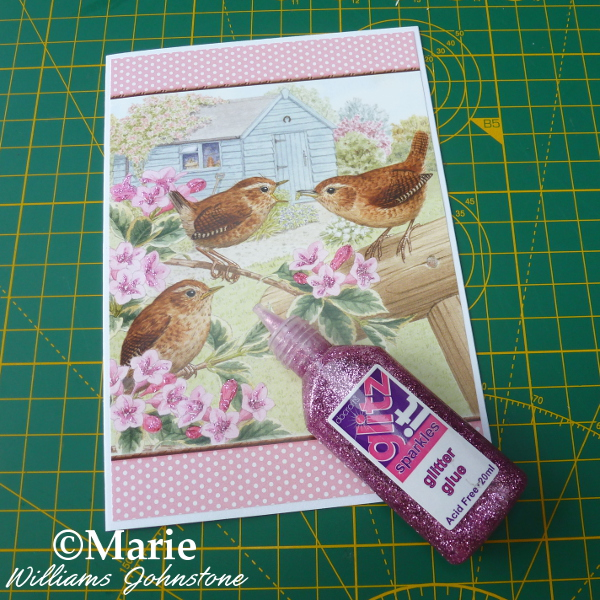 Adding pink glitter glue to the bird design by Hunkydory Little Books Little Book of Gardening