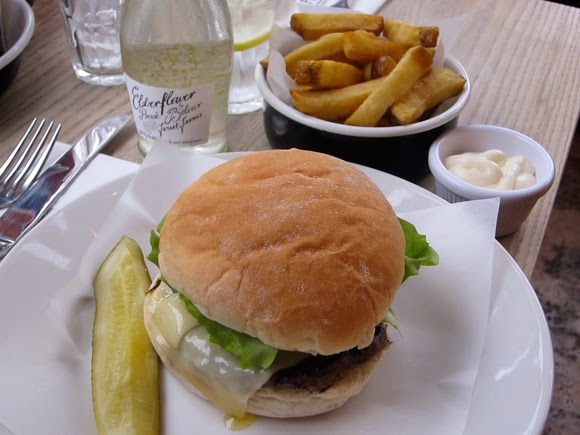 A shot of a burger, chunky chips, a gherkin, a pot of mayo and elderflower flavour juice at Byron proper hamburgers