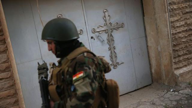 Seorang anggota milisi Kristen tengah berpatroli di jalan-jalan yang ditinggalkan di wilayah Telskuf, November 2015.