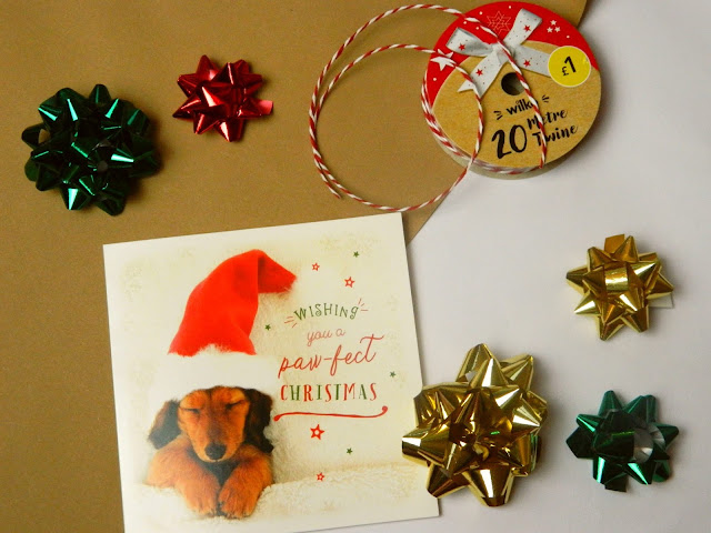 Supplies for wrapping Christmas presents: decoration, a christmas card, brown paper, festive paper string